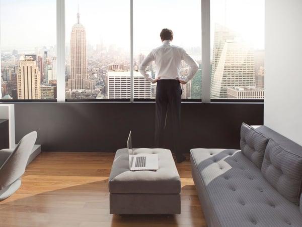 年轻人在他的豪华公寓里眺望着纽约天际线