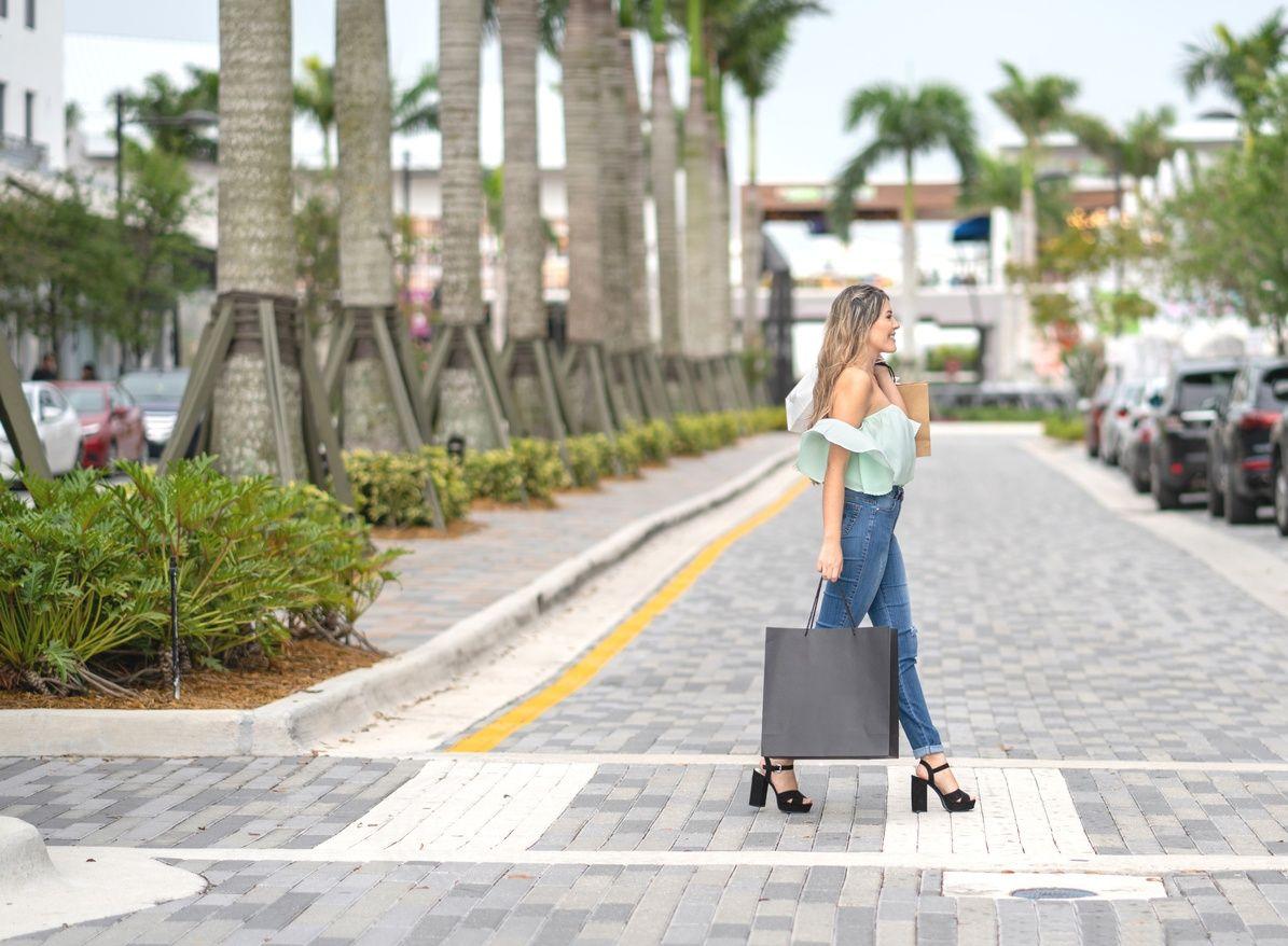 拎着购物袋过马路的妇女